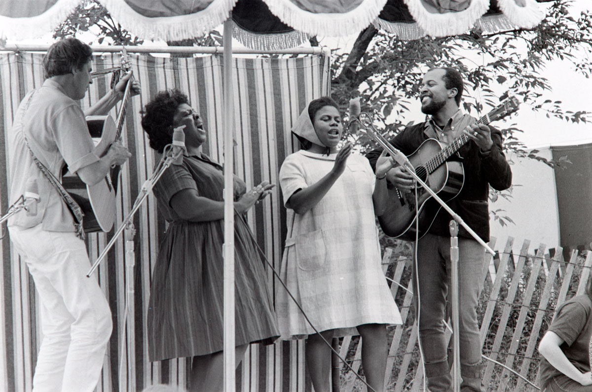 Musicians Guy Carawan, Fannie Lou Hamer, Bernice Johnson Reagon, and Len Chandler perform civil rights songs at the 1965 Newport Folk Festival.