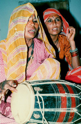 Methi singing and playing Dholak, accompanied by her sister.