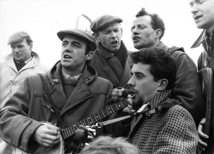 Scottish folk singers protest the presence of Polaris missiles in the Holy Loch while on board a ferry between Dunoon and Gourock, September 1961.  Josh MacRae is on the left playing the banjo, Morris Blythman is adjacent at center, and Nigel Denver is bottom center right.