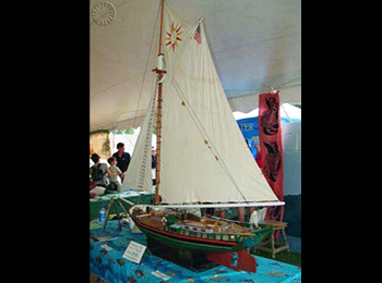 A model of the Clearwater sloop, which takes educational cruises along the Hudson River, on display in the Kids' Coast tent at the Folklife Festival. Clearwater staff teach children about the health of the river and its fishy inhabitants.