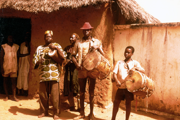 Image. Depicts four young men playing various drums while standing outdoors.
