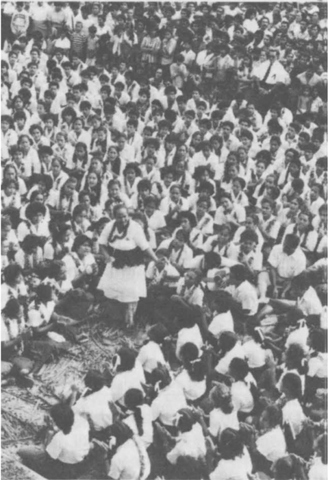 A taupou dancer performing in the middle of many singers.