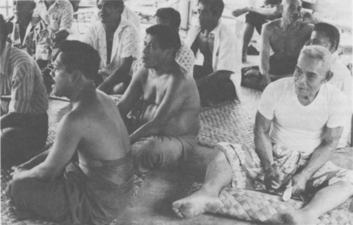 Adults of a Western Samoan community, sitting on mats singing and drumming.